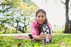 Healthy young asian woman exercising at park. Fit young woman doing training workout in morning. Young happy asian woman stretching at the park after a running Stock Images