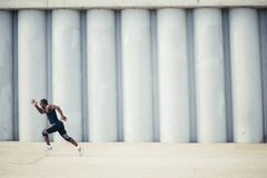 Healthy young athletic man running at the road royalty free stock photos