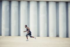 Healthy young athletic man running at the road royalty free stock photography
