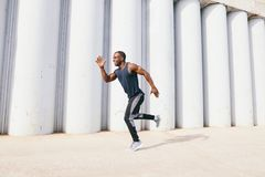Healthy young athletic man running at the road stock photography