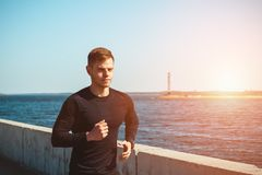 Healthy young black man jogging. At the beach Stock Image
