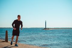 Healthy young black man jogging. At the beach Stock Photo
