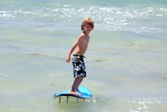 Healthy young boy learning to surf. In the sea or ocean Royalty Free Stock Image