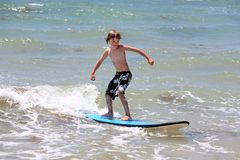Healthy young boy learning to surf. In the sea or ocean Royalty Free Stock Photography