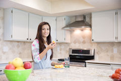 Healthy young brunette eating orange at the kitchen. Royalty Free Stock Photo
