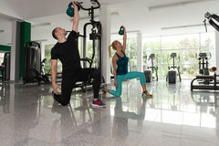 Healthy Young Couple Doing Exercise With Kettle Bell. Fitness Woman And Man Working With Kettle Bell In A Gym - Kettle-bell Exercise Stock Photo