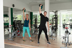 Healthy Young Couple Doing Exercise With Kettle Bell. Young Woman And Man Working With Kettle Bell In A Gym - Kettle-bell Exercise Royalty Free Stock Photo