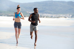 Healthy young couple running along the beach Stock Photography