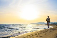 Healthy young fitness woman runner running on sunrise seaside tr. Ail royalty free stock image