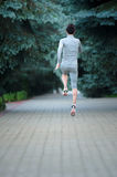 Healthy young fitness woman trail runner running at the park. Ba. The healthy young fitness woman trail runner running at the park. Back view royalty free stock image