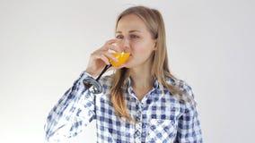 Healthy young girl drinks orange juice. Young woman with a glass of juice. Healthy young girl drinks orange juice. Young woman with a glass of orange juice stock footage