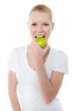 Healthy young girl eating nutritious green apple. Young girl eating nutritious green apple isolated over white Royalty Free Stock Images
