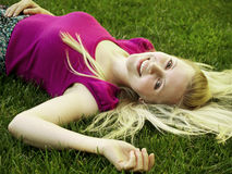 Healthy young girl laying on the grass Royalty Free Stock Photos