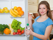 Healthy young girl taking a bottle of water out of fridge full o Royalty Free Stock Image