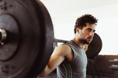 Healthy young guy at gym exercising with barbell. Fit young man working out with heavy weights at cross training gym Royalty Free Stock Photography