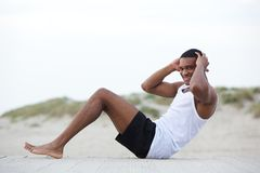 Healthy young man doing sit ups at the beach Stock Photos