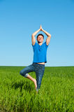 Healthy young man doing yoga against sky Stock Images