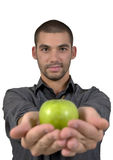 Healthy young man holding a green apple in the pal. Handsome young man smiling, holding a green crispy apple in the palm of his hands, on an isolated white Stock Image