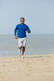 Healthy young man jogging at the beach Stock Photos