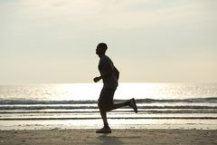 Healthy young man jogging on beach. Side view of a healthy young man jogging on beach Stock Images