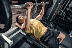 Healthy young man performs exercises on the chest. Lifting the barbell. Photos taken on an atmospheric old gym in a vintage atmosphere Royalty Free Stock Photos