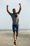 Healthy young man running with arms raised up Royalty Free Stock Photography