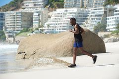 Healthy young man running on beach Royalty Free Stock Images