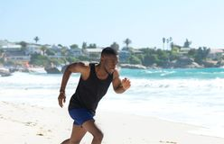 Healthy young man running on the beach Royalty Free Stock Images