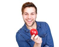 Healthy young man smiling. Close up portrait of a healthy young man smiling with apple in hand isolated on white background Stock Photo