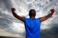 Healthy young man standing against sky. Rear view portrait of healthy young man standing against sky with arms outstretched Royalty Free Stock Image