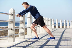 Healthy young man stretching outside for exercise Stock Photo