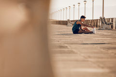 Healthy young man taking a break running session. Shot of healthy young man taking a break running session. Male runner stretching legs after running on Stock Image