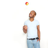 Healthy young man throwing apple in the air. Portrait of a healthy young man throwing apple in the air Royalty Free Stock Image