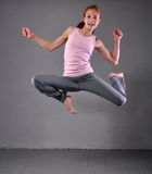Healthy young muscular teenage girl skipping and dancing in studio. Child exercising with jumping on grey background. Stock Photo