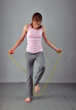 Healthy young muscular teenage girl skipping rope in studio. Child exercising with jumping high on grey background. Royalty Free Stock Image