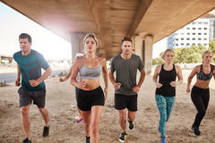 Healthy young people running together in city. Portrait of group of healthy young people running together in city. Running club members training together in Royalty Free Stock Image