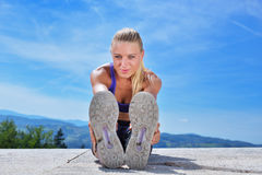 Healthy young pretty woman stretching her leg during exercise in park. Stock Photos