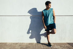 Healthy young runner standing by a wall. Full length shot of healthy young male runner leaning to a wall outdoors and looking away. Fitness man relaxing after Stock Photo
