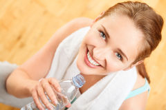 Healthy young sportswoman drinking water at gym Stock Photography