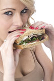Healthy Young Woman Biting in to a Sandwich Royalty Free Stock Photography