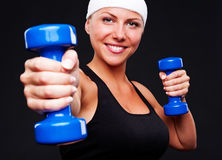 Healthy young woman with blue dumbbells Royalty Free Stock Images
