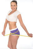 Healthy Young Woman Checking Her Weight Loss With a Tape Measure. A DSLR Royalty free image, of attractive healthy fit young woman, standing happily with stock photos