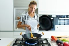 Healthy Young Woman Cooking And Mixing Food In Frying Pan In The Kitchen At Home. Stock Images