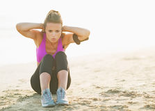 Healthy young woman doing abdominal crunch on beach Royalty Free Stock Photos