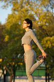 Healthy young woman doing exercise outdoors in park Royalty Free Stock Photography