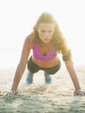 Healthy young woman doing push ups on beach Royalty Free Stock Photo