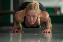 Healthy Young Woman Doing Push-ups On Floor. Young Woman Athlete Doing Pushups As Part Of Bodybuilding Training Royalty Free Stock Images
