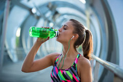 Healthy young woman drinking water and listening to music after exercising. Royalty Free Stock Images