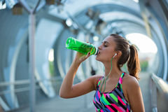 Healthy young woman drinking water and listening to music after exercising. Royalty Free Stock Photos