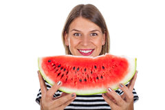 Healthy young woman eating watermelon. Picture of a healthy young woman eating a big slice of delicious watermelon posing on isolated background Royalty Free Stock Image